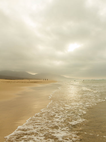 cloudy sky covers the beach as people walk by