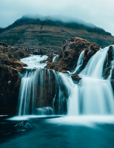 cloudy waterfall at the base of a mountain