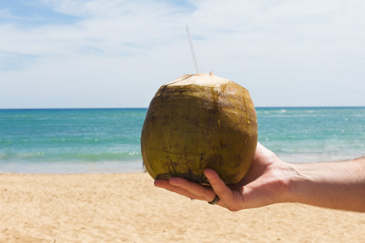 Coconut With Straw On Beach