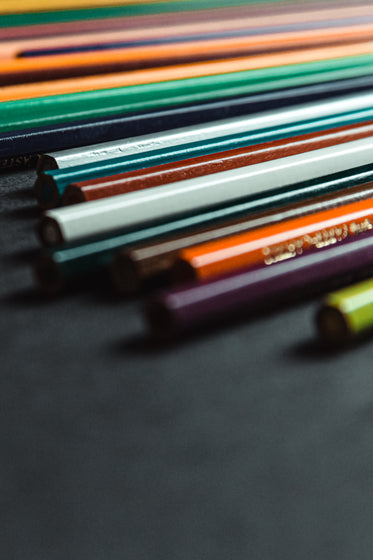 colored pencils lines up on a black background
