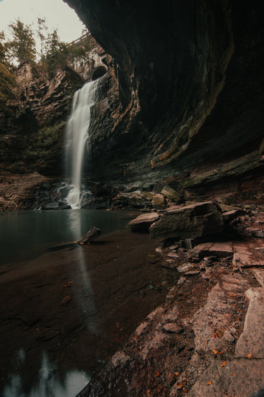 concaved rock face by waterfall