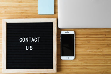 contact us sign with phone on desk