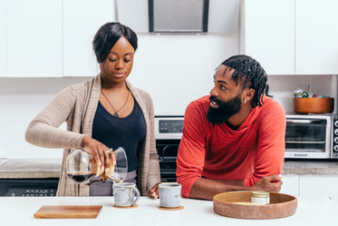 couple chat and make coffee in their kitchen