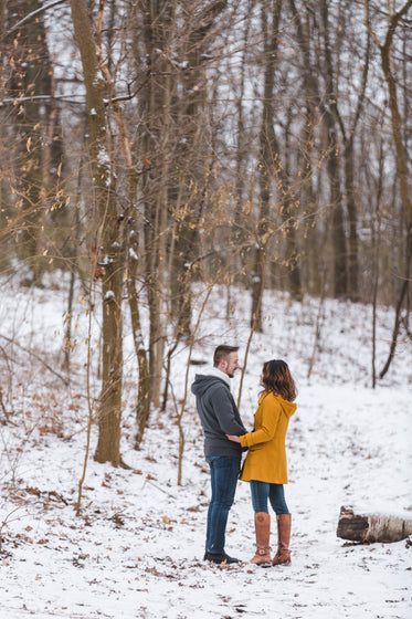 couple holds each other on a stroll in the snow