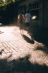 couple holds hands and walks on stone sidewalk