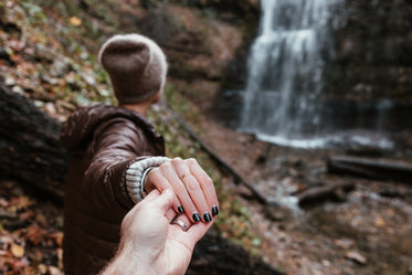 couple holds hands hiking waterfalls