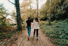 couple holds hands walking through green and yellow trees