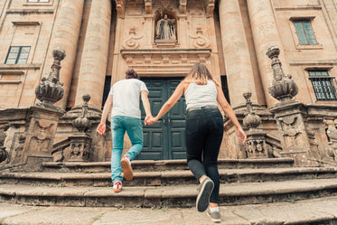 couple holds hands walking up stone steps