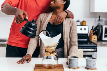 couple hug as they pour a cup of coffee