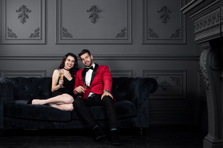 Couple In Formal Wear Cozy Up With Champagne