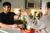 couple raises their glasses to cheers in their kitchen