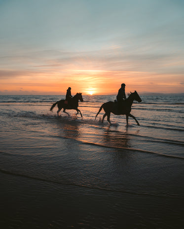 couple rides horseback on a sunset beach