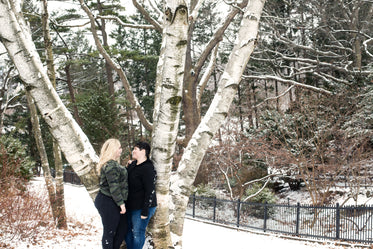 couple shares a loving look near a tall tree