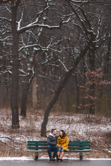 couple shares a warm laugh on a park bench in the winter