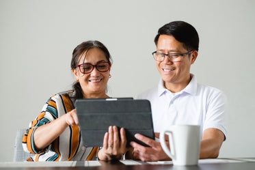 couple smile as the use a tablet