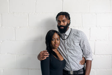 couple stand against white wall looking at camera