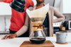 couple stand together pouring coffee