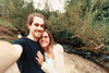 couple stands by a river and take a selfie