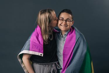 couple wrapped in pride flag kiss