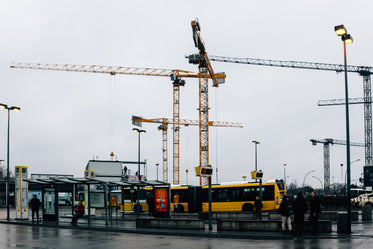 cranes hover over buses