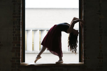 dancer bends back in window