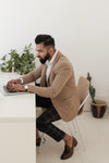 dapper store owner working on laptop