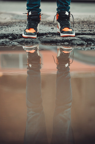 dark denim jeans and fashion sneakers reflect in city puddle