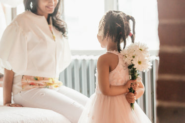 daughter about to suprise mom with flowers