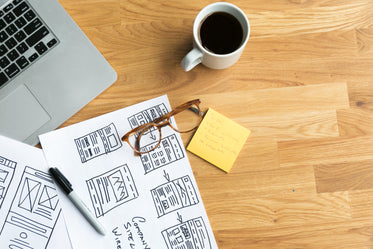 designer's desk with coffee and wireframes