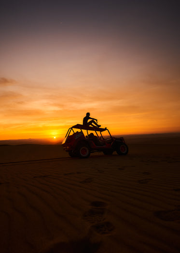dune buggy in front of setting sun