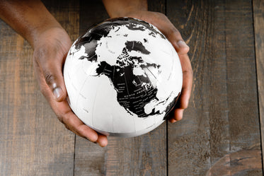 Person holding the world globe of the Earth on hand