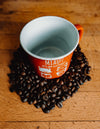 empty cup surrounded by coffee beans
