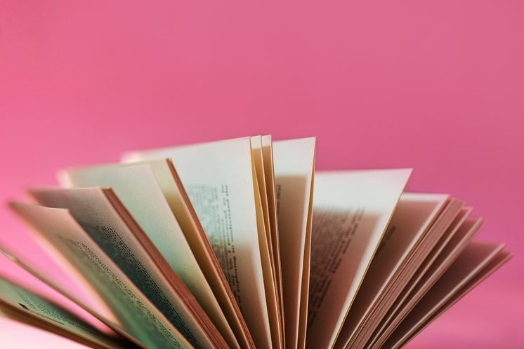 Fanned Out Book Pages Against A Pink Background