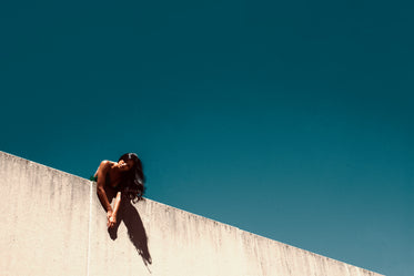 fashion model poses over cement wall and blue sky