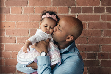 father gives baby daughter a kiss