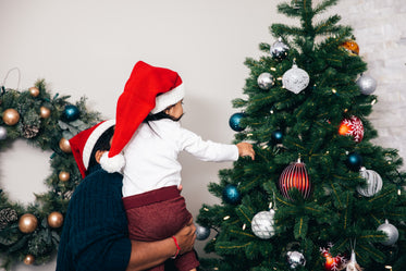 father helps toddler decorate christmas tree