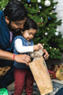 father helps toddler open christmas gifts