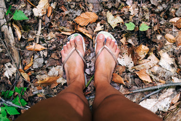 feet in sandals on fall leaves
