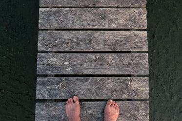 feet on a dock over rocky sandy ground