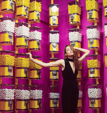 female model poses in front of gumball machine covered walls