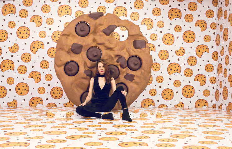Female Model Poses On Floor In Front Of Giant Cookie