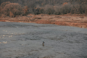 fisherman stands in a large river