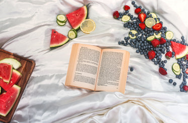 flatlay of a open book surrounded by fresh fruit on white silk