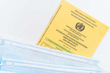 flatlay of a yellow vaccination card and facemasks