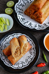 flatlay of plated spring rolls with hot peppers and limes