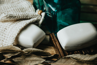 flatlay of two bars of white soap and dried leaves