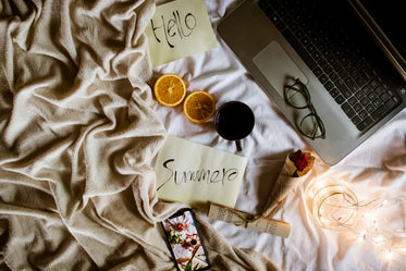 flatlay welcoming summer with a laptop and cellphone