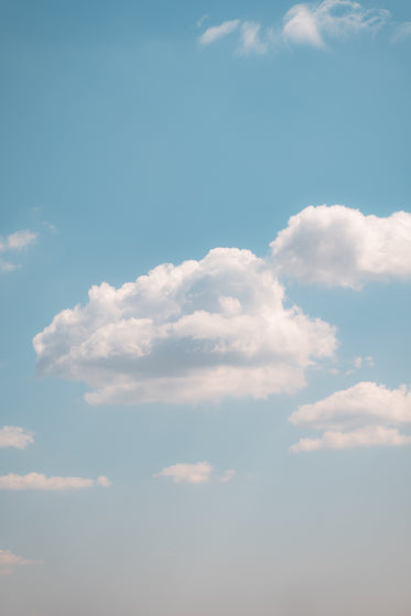 fluffy clouds in a light blue sky on a clear summer day