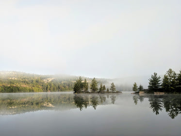 foggy landscape reflected in lake