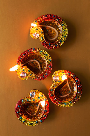 four candlelit diya lamps rest on brown background